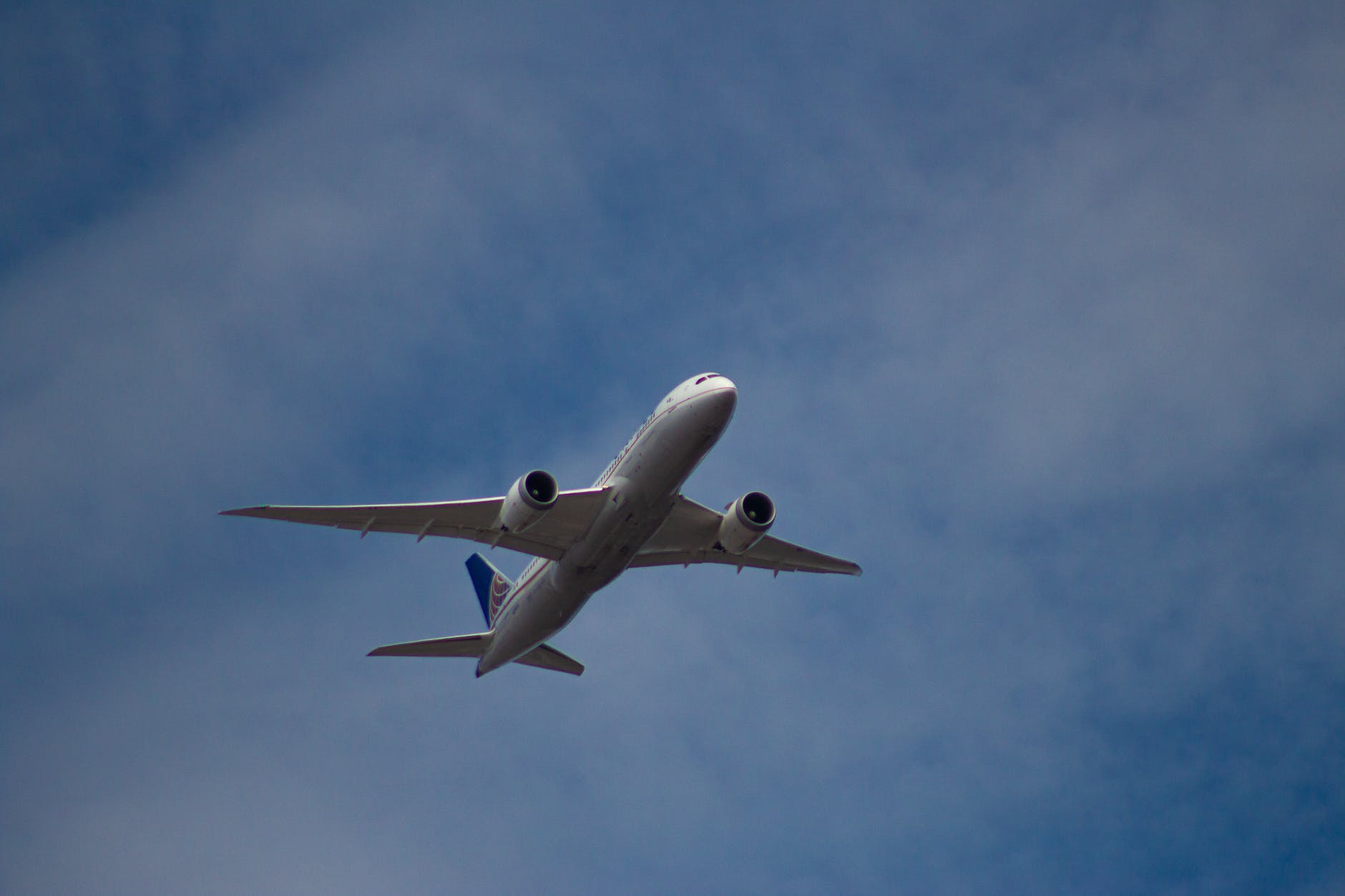airplane flying high in blue cloudy sky