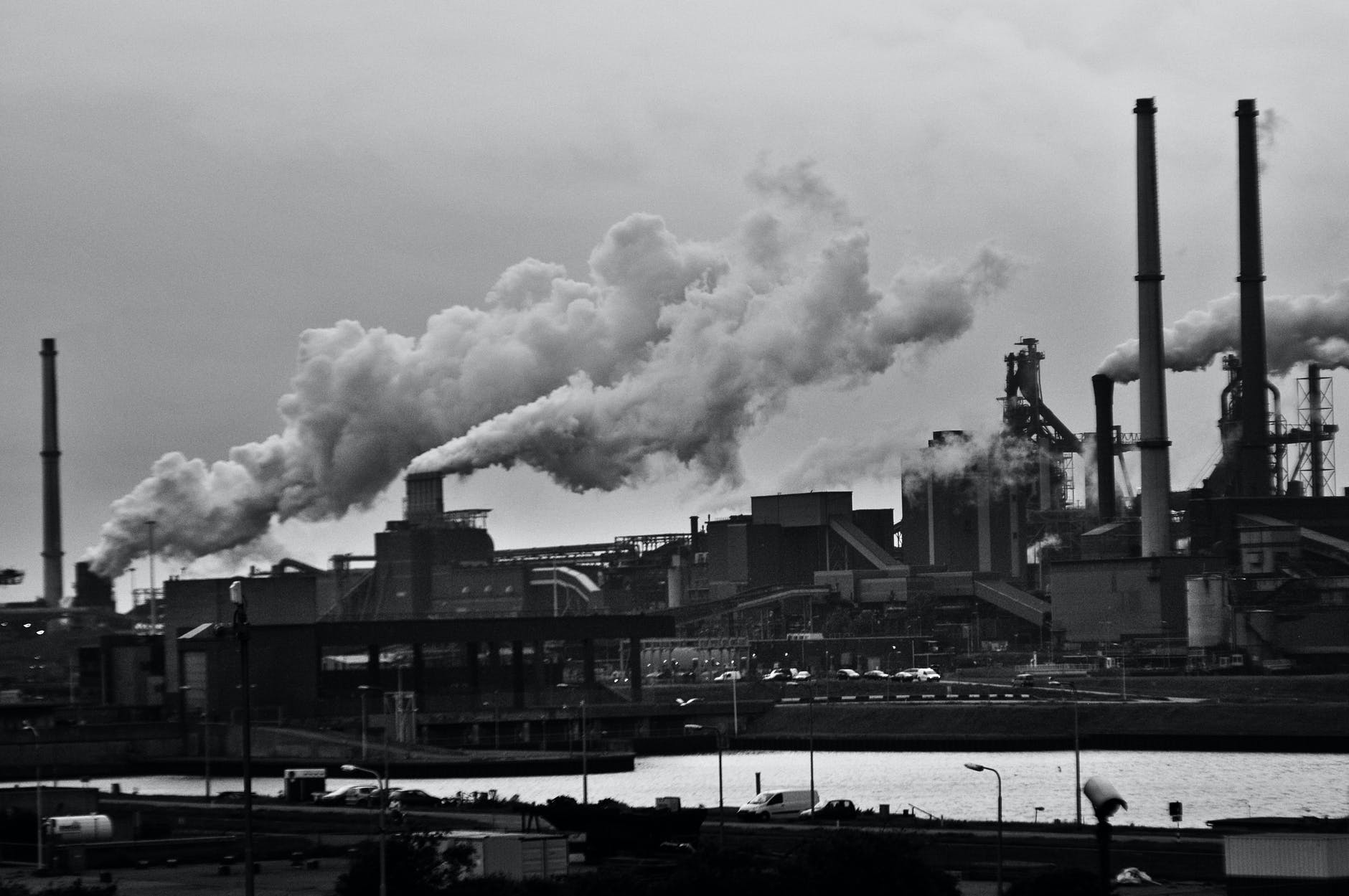 grayscale photography of locomotive train beside factory